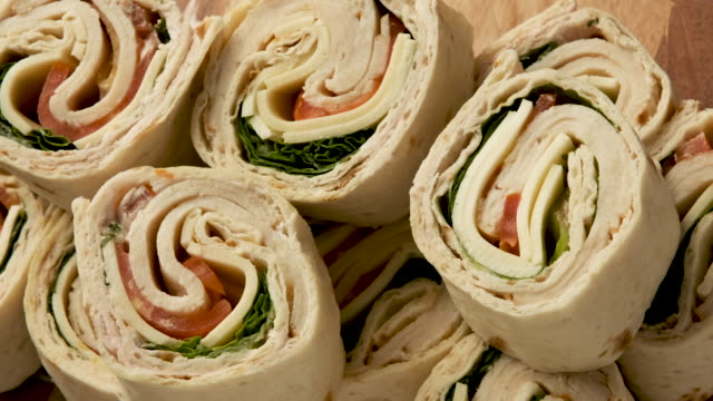 sliced turkey meat and cheese wrap sandwich - rotolo video stock e b–roll