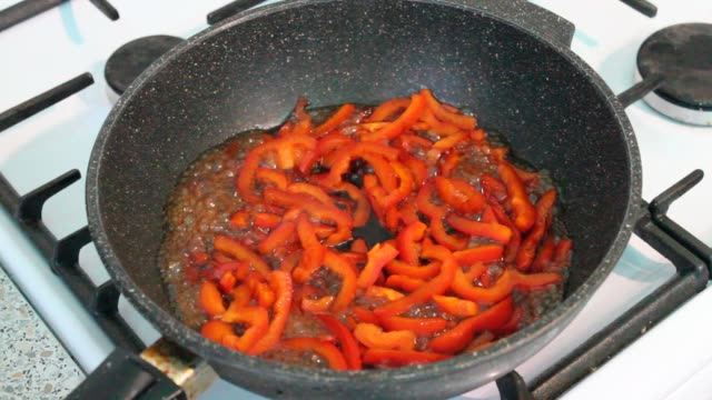 slices of bell pepper or paprika in the cooking process with soy sauce. ingredient cooking. background red pepper in a pan. - жареный на большом огне стоковые видео и кадры b-roll