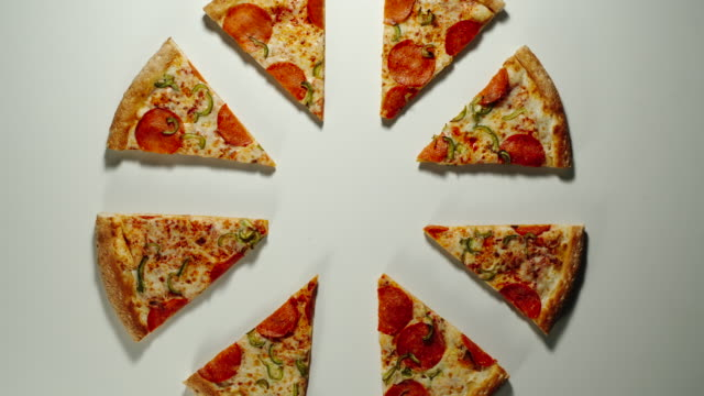 vídeos de stock e filmes b-roll de slices of big pizza is eaten up on a white surface in different directions - pizza