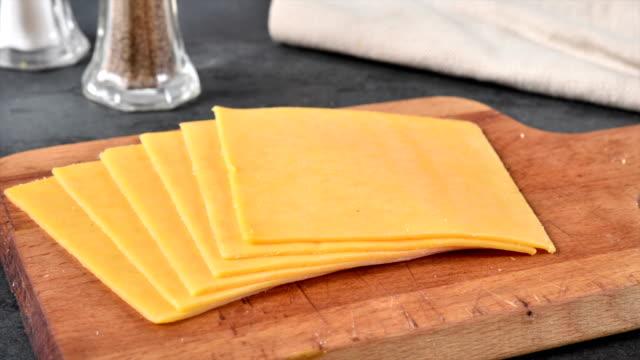 fette di formaggio cheddar che svaniscono - fetta video stock e b–roll