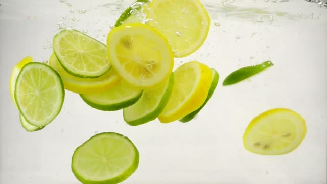Slices of citrus lime and lemon fall into the water with splashes and bubbles, slow motion close-up