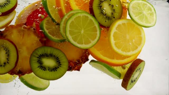 Slices of different fruits fall into the water, multifruit juice, slow motion close-up