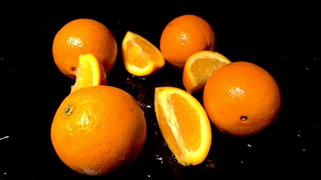 Slices Of Orange Falling On Black Background video