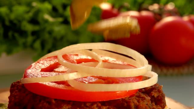 slices of pickled cucumber fall on a cheeseburger - cebula filmów i materiałów b-roll