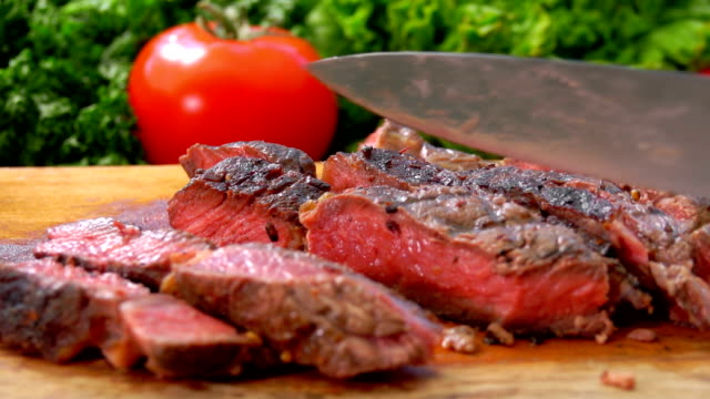 vídeos de stock e filmes b-roll de slices of prepared meat steak turned with a knife - beef angus