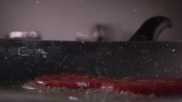 Tranches de tomates étant laissé tomber et frit dans une poêle dans l'huile qui grésille. Slow motion - Vidéo