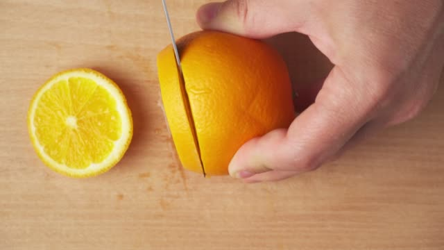 Slicing an orange on a kitchen cutting Board and putting on a plate, wooden table as background, close view.