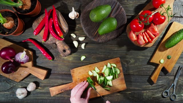 Slicing and chopping fresh vegetables on the wooden table Slicing and chopping various fresh vegetables on the dark wooden table using natural wooden cutting boards. Vegan conception kitchen utensil stock videos & royalty-free footage