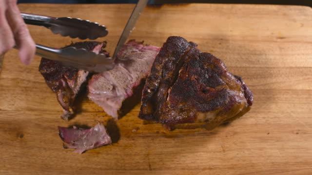 Slicing barbequed pork shoulder Slicing smoked barbequed pork shoulder on a wooden cutting board. pork stock videos & royalty-free footage