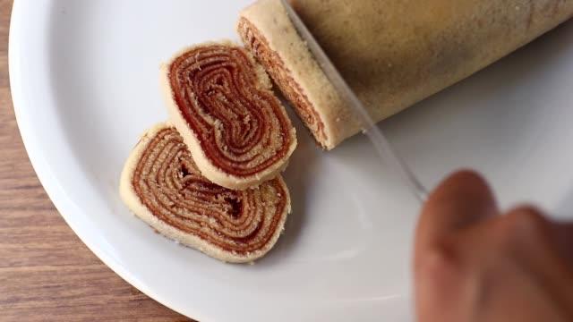 vídeos de stock, filmes e b-roll de cortando bolo de rolo. corte de fatia de bolo de rolo (rolo suíço, bolo de rolo) sobremesa brasileira em prato branco no fundo de madeira - nordeste