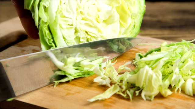 Slicing cabbage on wooden cutting board Slicing cabbage with kitchen knife on wooden board, isolated on black background cabbage stock videos & royalty-free footage