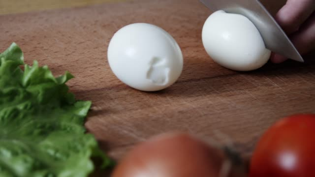 slicing hard boiled eggs in half. man cuts eggs on chopping board with knife in kitchen. cutting ingredients for salad. - варёный стоковые видео и кадры b-roll