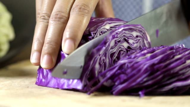 Slicing purple cabbage with kitchen knife on wooden board, close up. Slicing purple cabbage with kitchen knife on wooden board, close up, uhd 4k. cabbage stock videos & royalty-free footage