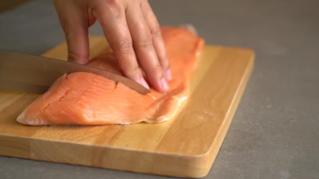 slicing salmone su legno a bordo - filetto video stock e b–roll
