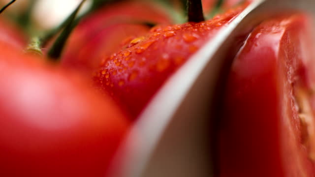 Slicing tomato macro shot video