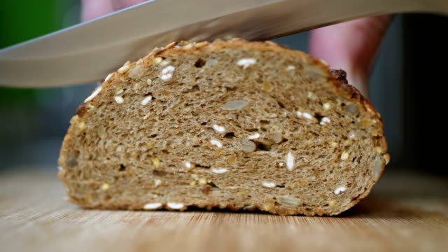 Slicing Whole Grain Bread On Wooden Table video