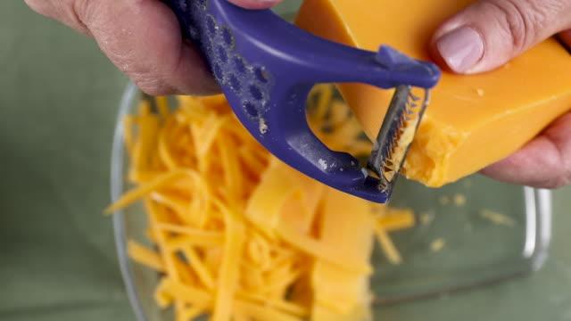 affettando il formaggio cheddar giallo da vicino. ingrediente per cucina casalinga - a forma di blocco video stock e b–roll