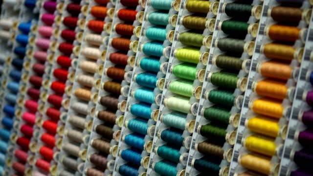 far scorrere in basso su molti fili multicolore confezioni rack in negozio - cilindro video stock e b–roll