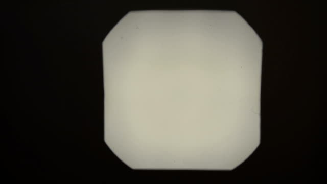 Slide Projector Retro styled footage with audio of blank slides being projected against a dark wall, with copy space for your text projection stock videos & royalty-free footage