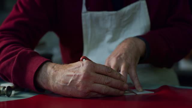 vídeos y material grabado en eventos de stock de toma deslizante de un banco zapatero con algunas telas y herramientas en una fábrica de zapatos italiana. - piel textil