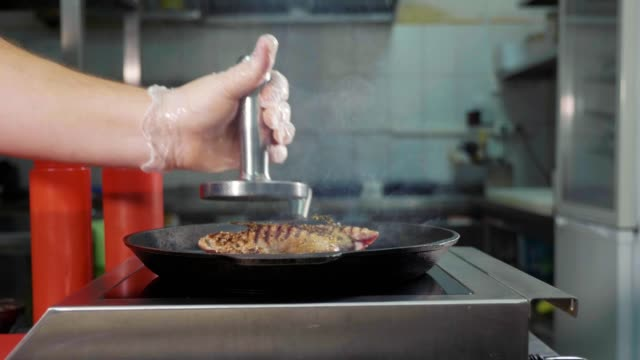 Slide slow motion of chef puts a steel press on steak of meat on a griddle pan video