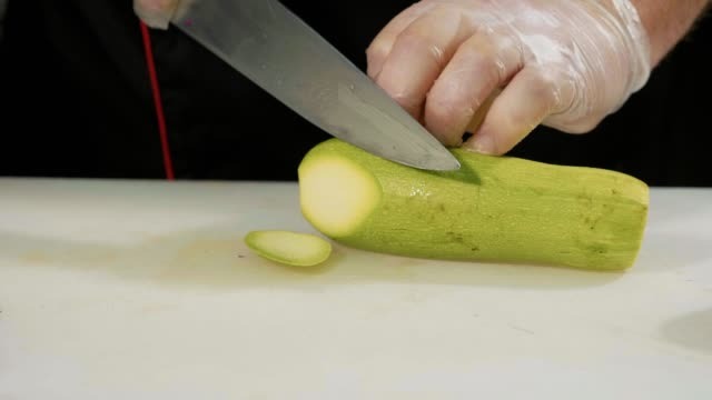 Slide slow motion of professional chef chopping vegetables, close-up video