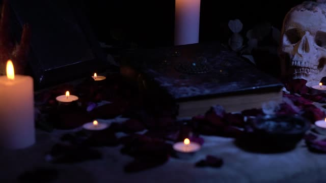 Schieberegler Dreharbeiten ein Zauberbuch und einem Totenkopf unter Kerzen – Video