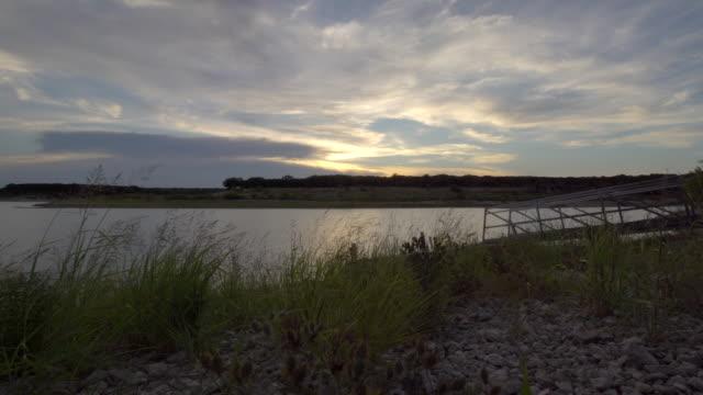 Slider Shot of Boat On Large Lake During Colorful Sunset