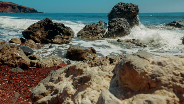 Slider Shot of Mediterranean Volcanic Beach with Red Sand and Surf Hitting the Rocks video