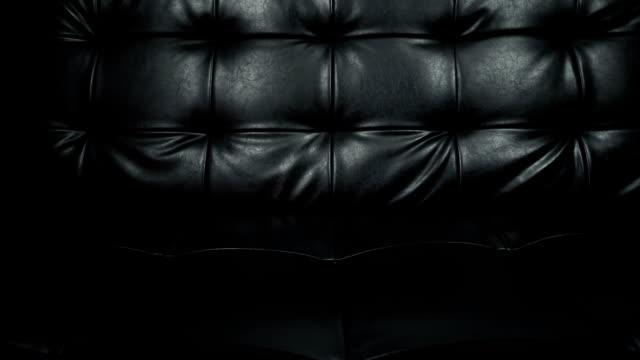 stockvideo's en b-roll-footage met slider shot van textuur van mooie zwarte lederen sofa, twee schoten - dierenhuid huid