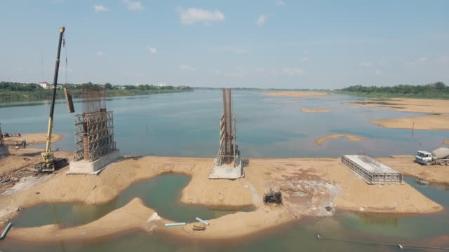 slider shot to the new bridge being assembled in segments lifted out of the water by  crane truck video