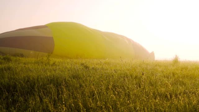 kamera sürgülü. şişirilmiş sıcak hava balonu. güneşin doğuşunda uçuş hazırlığı. sisli sabah. çimen 4k üzerinde parlayan çiy - zeplin stok videoları ve detay görüntü çekimi