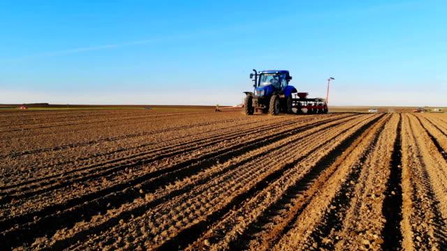 vídeos de stock e filmes b-roll de sliding shot of tractor seeding - trator