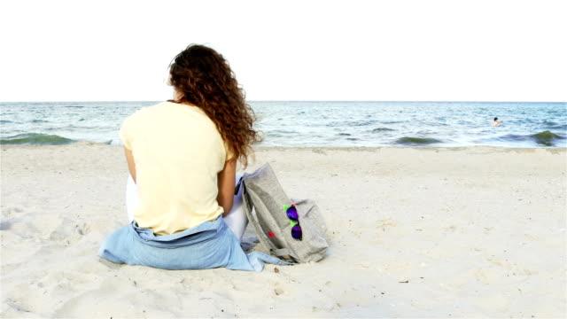 stockvideo's en b-roll-footage met curly brunette slank met koptelefoon luisteren naar muziek op het strand en kijkt naar de horizon, uitzicht vanaf de achterkant - curly brown hair
