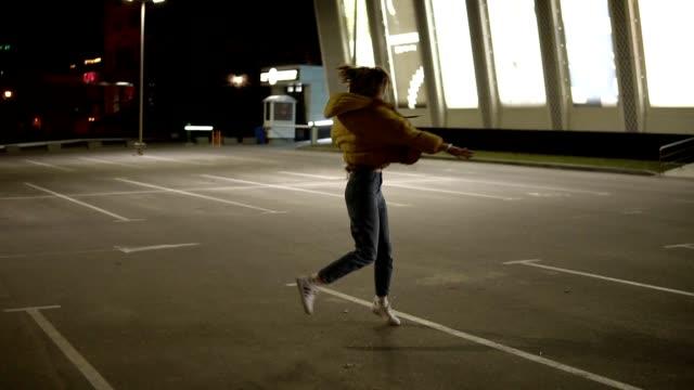 schlanke, zarte mädchen in graue hose und gelben mantel tanzt und hat spaß auf dem parkplatz außerhalb - hipster stock-videos und b-roll-filmmaterial