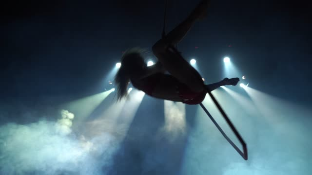 Slim female Aerial acrobat on the stage with aerial hoop with spot lights on background