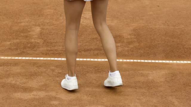 スリムな女性アスリート ジャンプとクローズ アップのコートでテニス ・ ボールをヒットする準備をして - 女性選手点の映像素材/bロール