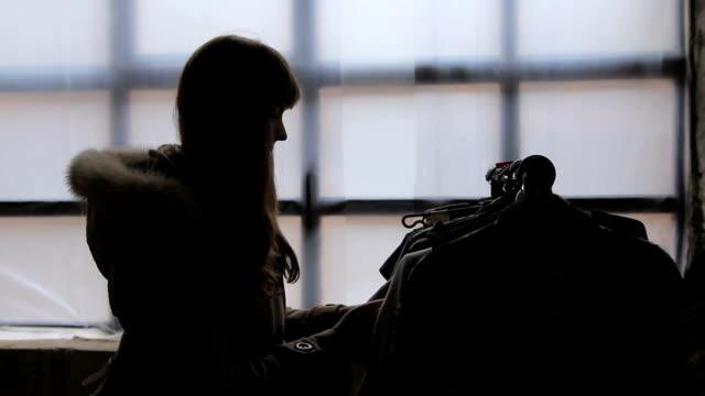 vídeos de stock, filmes e b-roll de silhueta feminina magro, procurando roupas fora de moda vintage em brechó - arméria