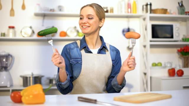 Slim girl choosing between vegetable and sausage, organic food vs gmo products