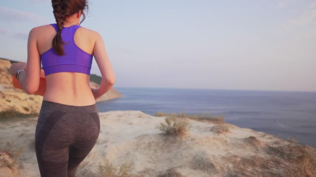 slim girl goes next to a cliff with a rug for playing sports or yoga. sunset or dawn by the ocean. - posizione corretta video stock e b–roll