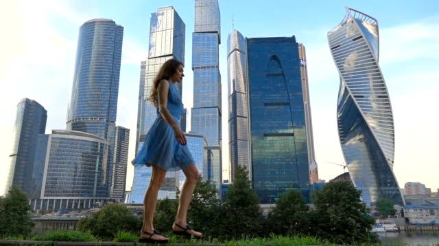vídeos y material grabado en eventos de stock de chica delgada en vestido azul caminar contra los rascacielos modernos, vídeo de cámara lenta súper, 250 fps - moda playera