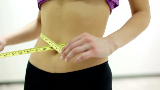 Slim girl measuring waist with yellow ribbon video