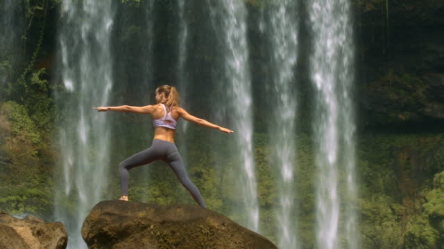 Slim Girl Poses on Round Rock against Waterfall Backside view slim girl with ponytail poses in yoga exercise on large round rock against waterfall streams seductive women stock videos & royalty-free footage