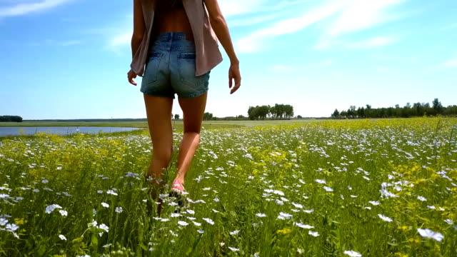 slim girl with long hair in shorts walks on buckwheat field