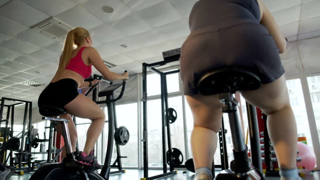 Slim lady and overweight female riding exercise bikes in gym, competition video