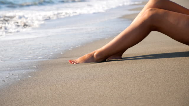 Slim legs of woman lying on tropical beach with splashing waves. Ocean tides washing over tanned female feet. Girl relaxing on coast during summer vacation. Summer holiday concept. Dolly shot Slim legs of woman lying on tropical beach with splashing waves. Ocean tides washing over tanned female feet. Girl relaxing on coast during summer vacation. Summer holiday concept. Dolly shot resting stock videos & royalty-free footage