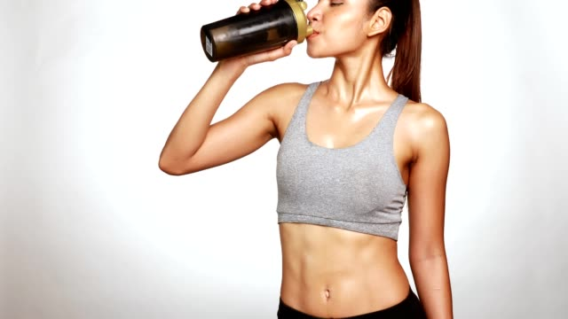 Slim perfect female body in sportswear drinking a whey protein supplement for fitness and diet to control video