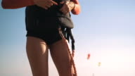 istock Slim sexy kitesurfer girl checking her wetsuit and floatation vest before riding on water. Woman professionally fasten lines around the rash vest. Basic preparation procedures of kite and board before launching on water 1169831943