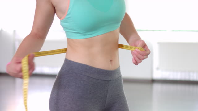 Slim woman measuring waist in aerobics class video