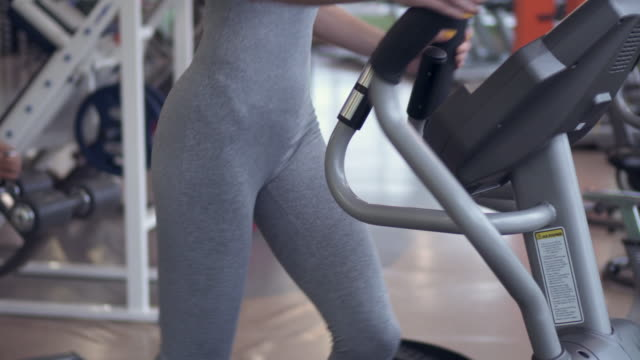 Slim woman using cross trainer at the gym video